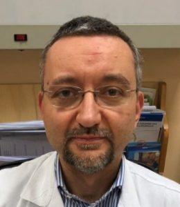 uomo con occhiali con camice da medico